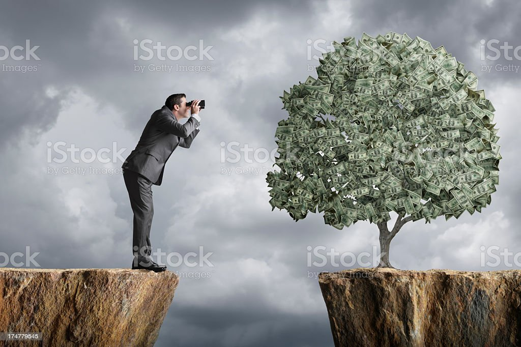 Businessman using binoculars to view a money tree royalty-free stock photo