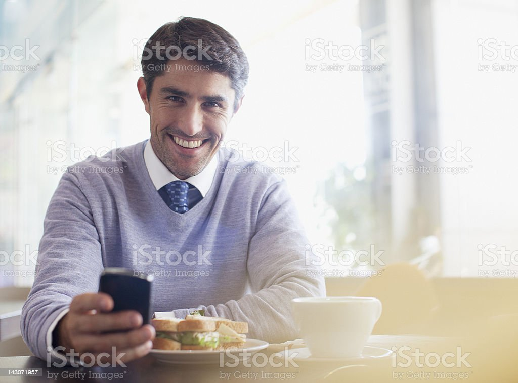 Businessman using cell phone in cafe stock photo