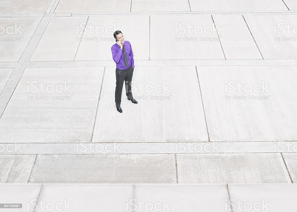 Businessman using cell phone in courtyard royalty-free stock photo