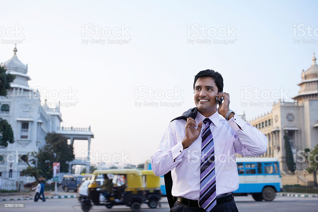 Businessman Using Cell Phone On City Street stock photo