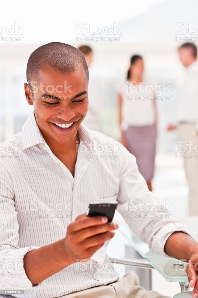 Businessman using cellphone with colleagues in the background royalty-free stock photo
