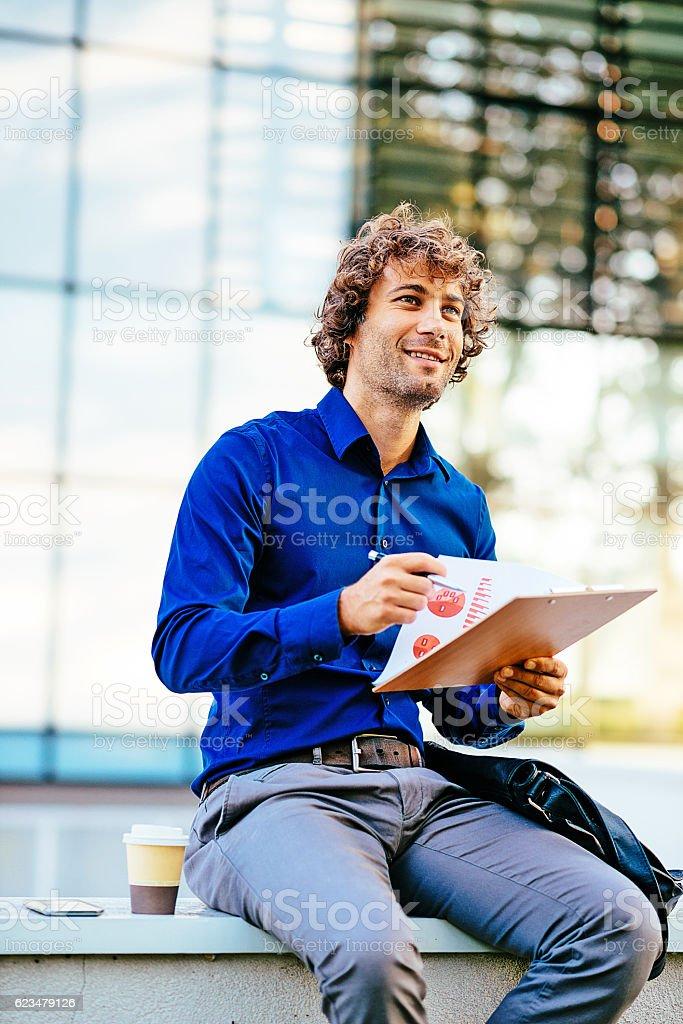 Businessman using coffee break for data analysis stock photo