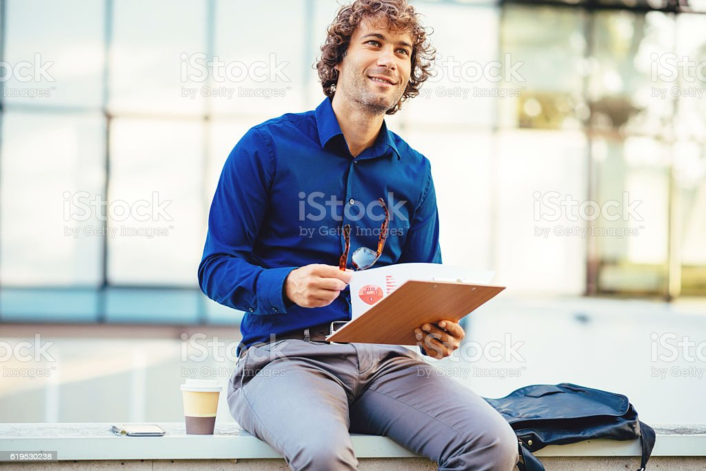 Businessman using coffee break for data digging stock photo