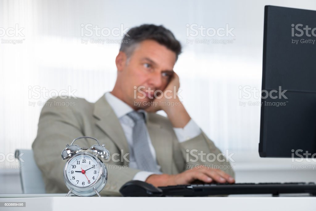 Businessman Using Computer At Desk With Focus On Clock stock photo
