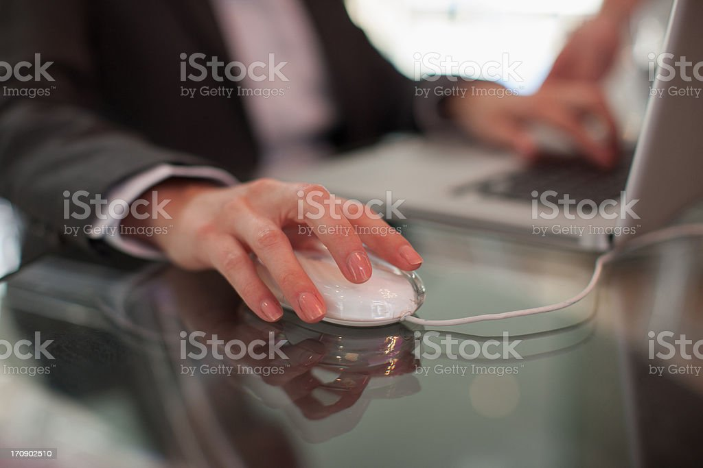 Businessman using computer mouse and typing on laptop royalty-free stock photo