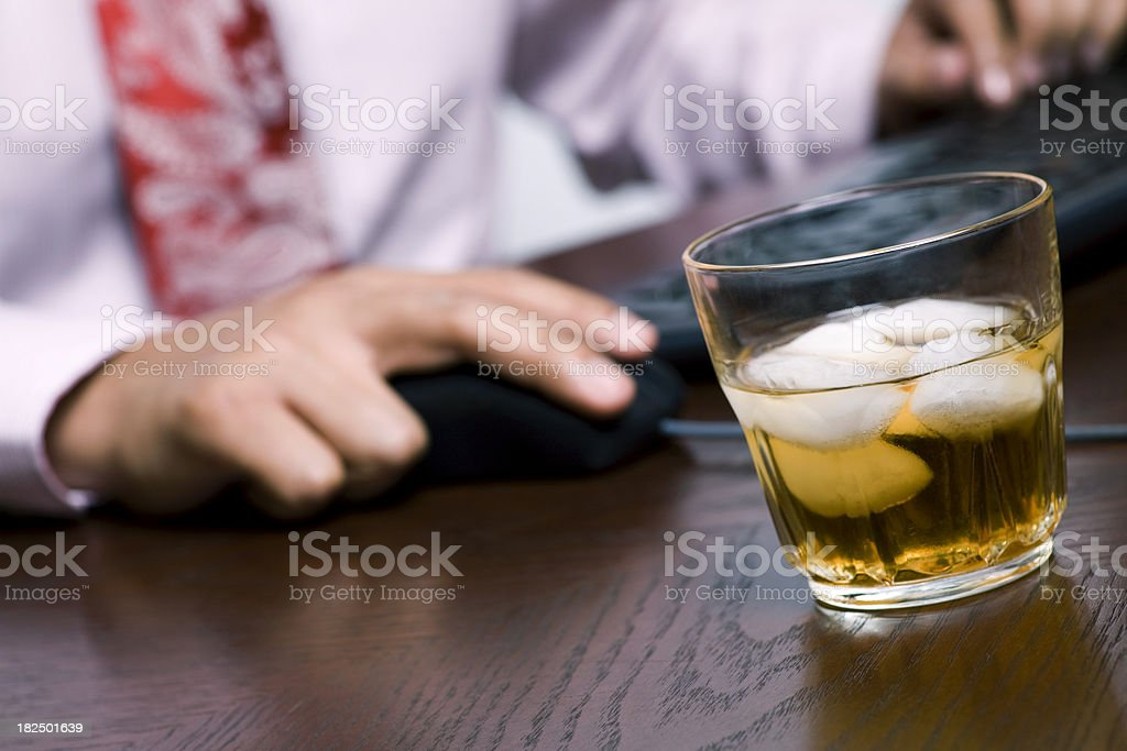 Businessman using computer next to a glass of whiskey royalty-free stock photo