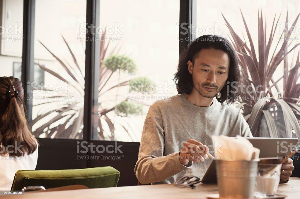 Businessman using digital tablet at cafe stock photo