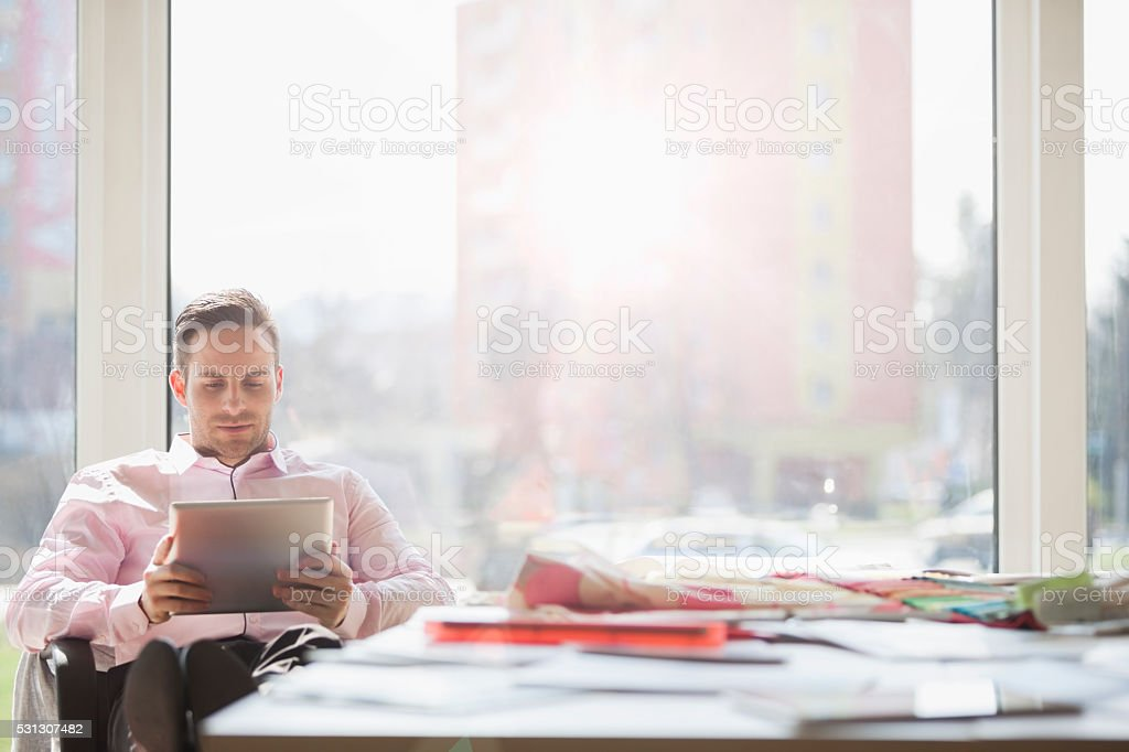 Businessman using digital tablet at conference table in creative office stock photo