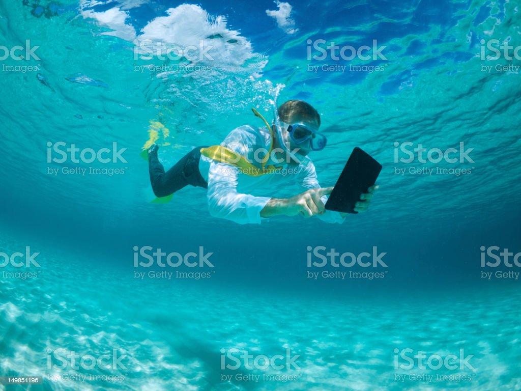 Businessman Using Digital Tablet Computer Underwater Snorkeling stock photo