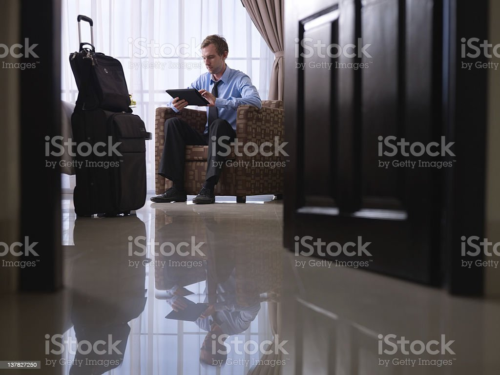 Businessman using digital tablet pc in hotel room stock photo