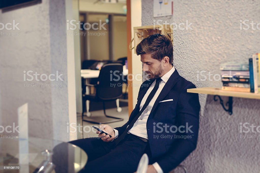 Businessman using his phone in an open lobby. stock photo
