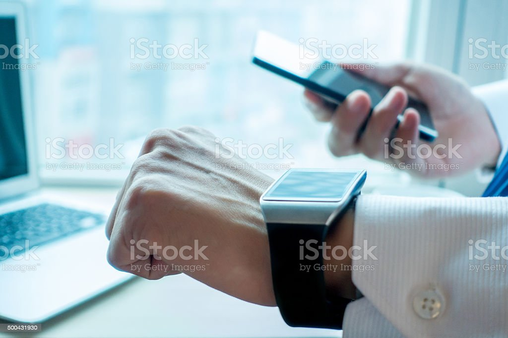 Businessman using his smartwatch and phone in office stock photo