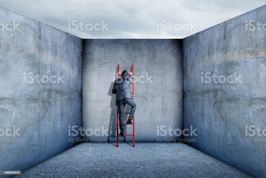 Businessman Using Ladder To Escape stock photo