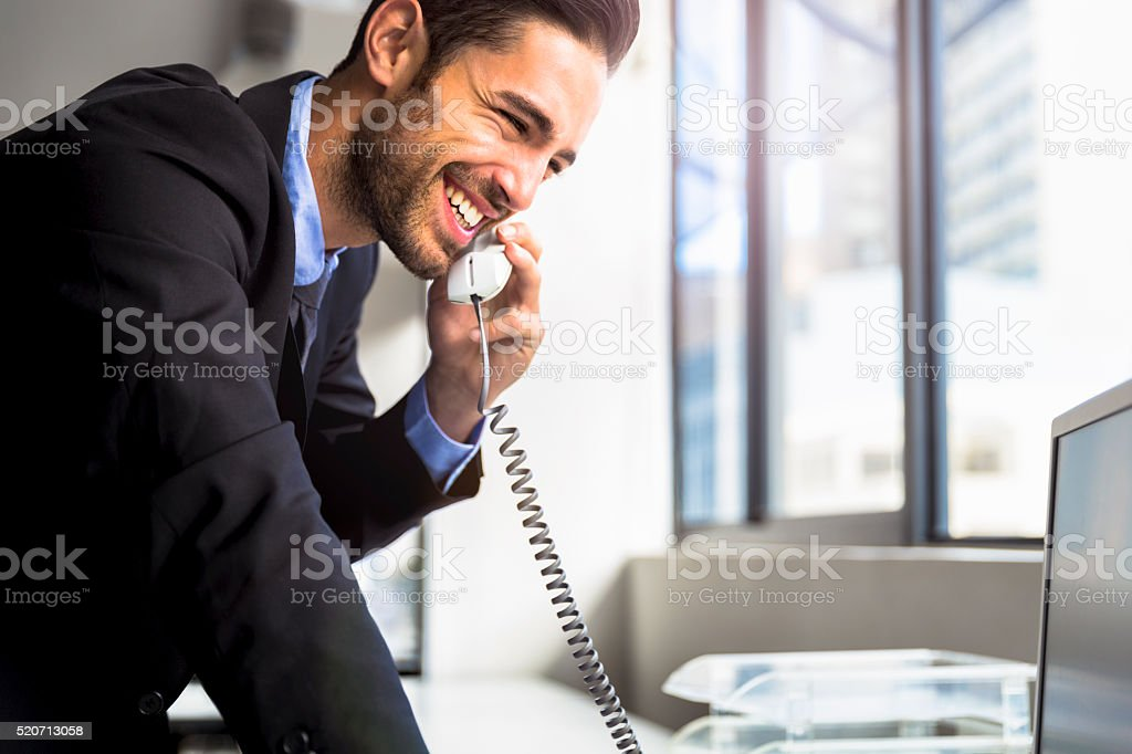 Businessman using landline phone in office stock photo