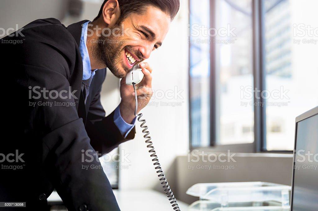 Businessman using landline phone in office stock photo