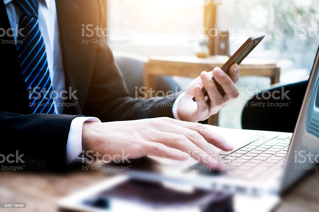 Businessman using laptop and holding mobile phone stock photo