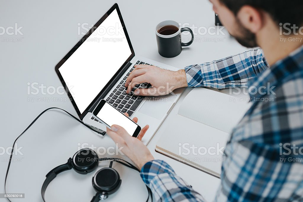 businessman using laptop and phone with blank screen stock photo