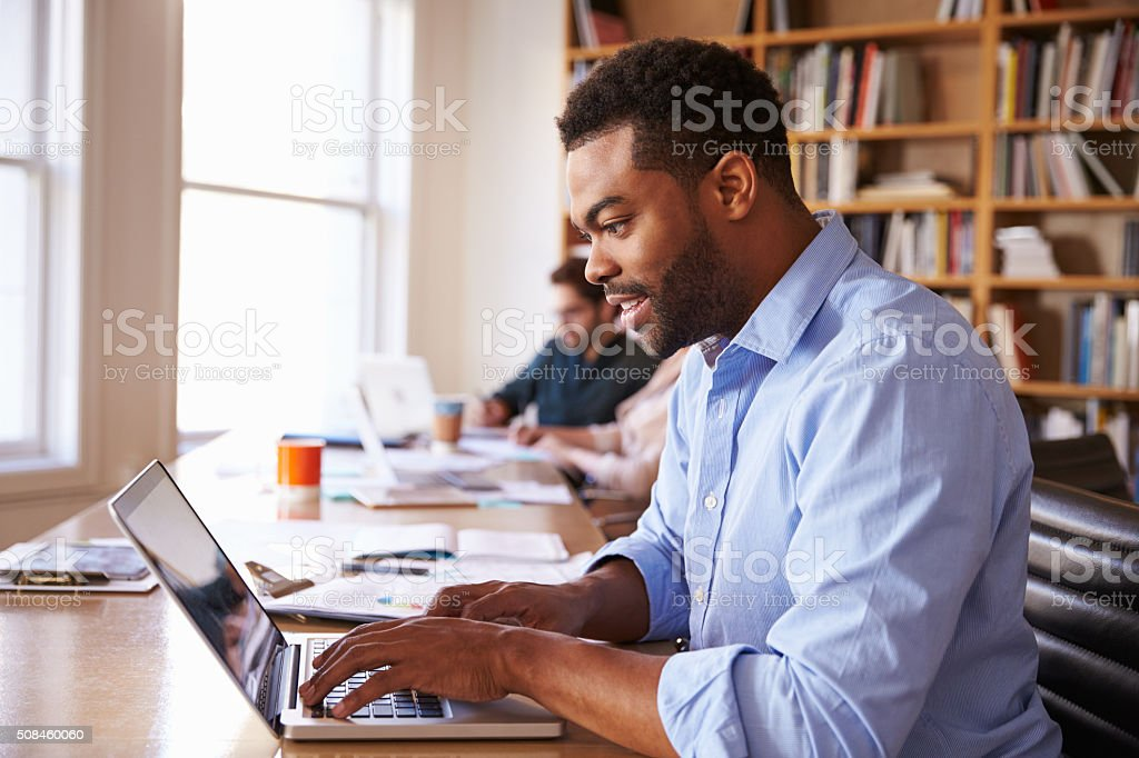 Businessman Using Laptop At Desk In Busy Office stock photo