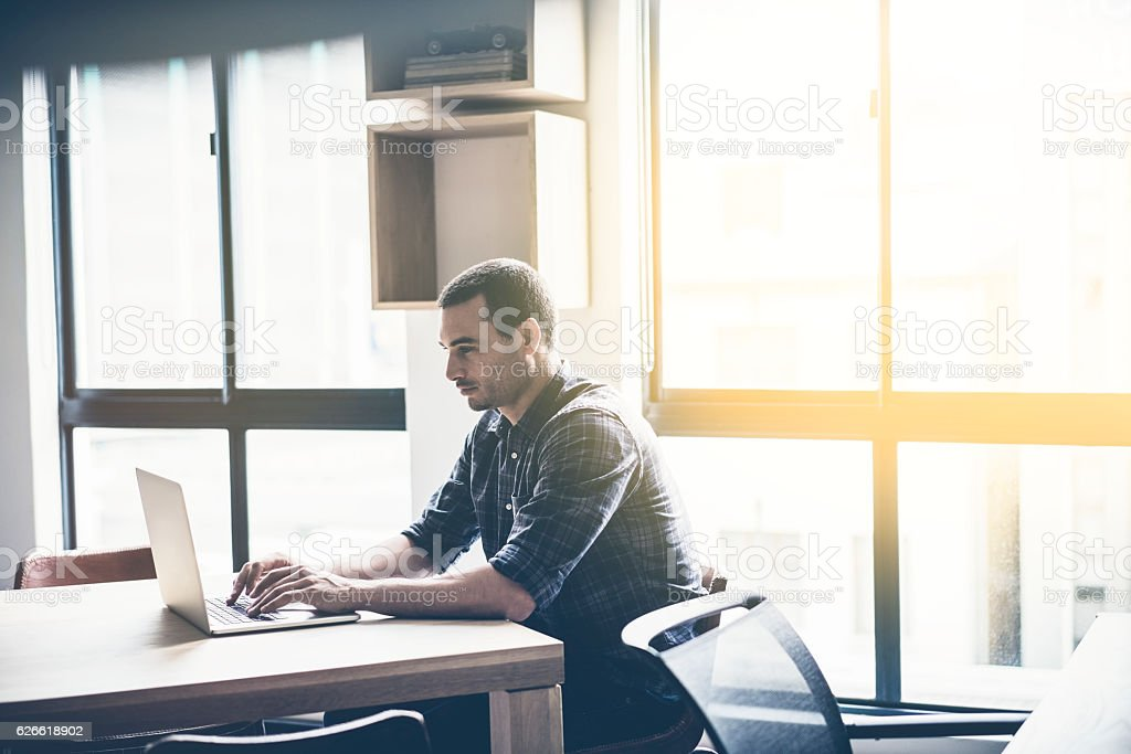 Businessman using laptop at desk in office stock photo