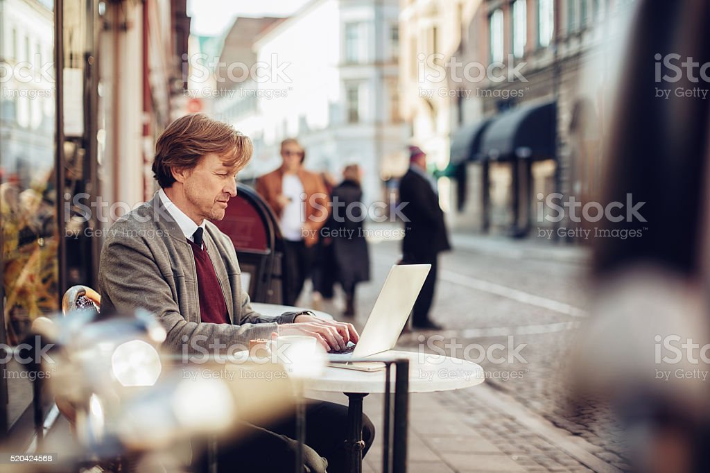 Businessman using laptop at sidewalk cafe stock photo