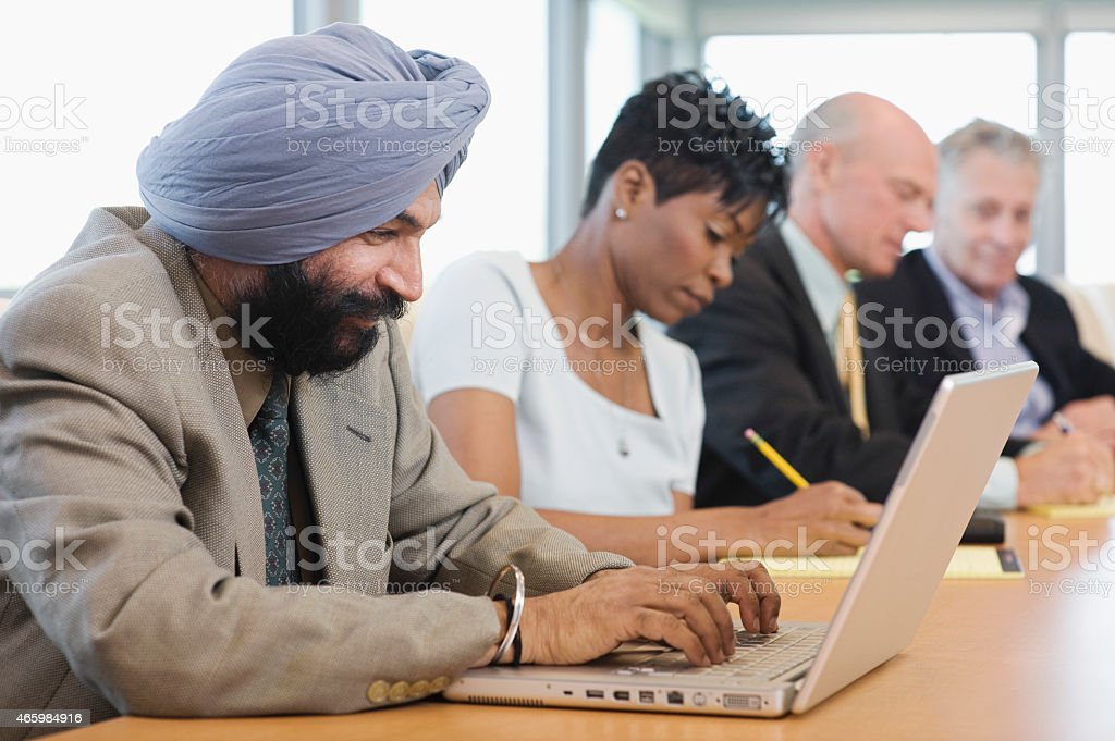 Businessman Using Laptop Besides Multiethnic Colleagues stock photo