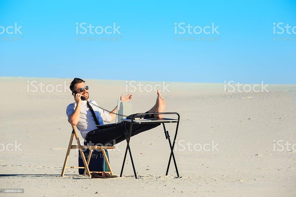 Businessman using  laptop in a desert stock photo