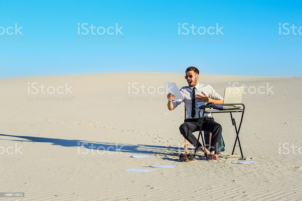 Businessman using  laptop in a desert stock photo