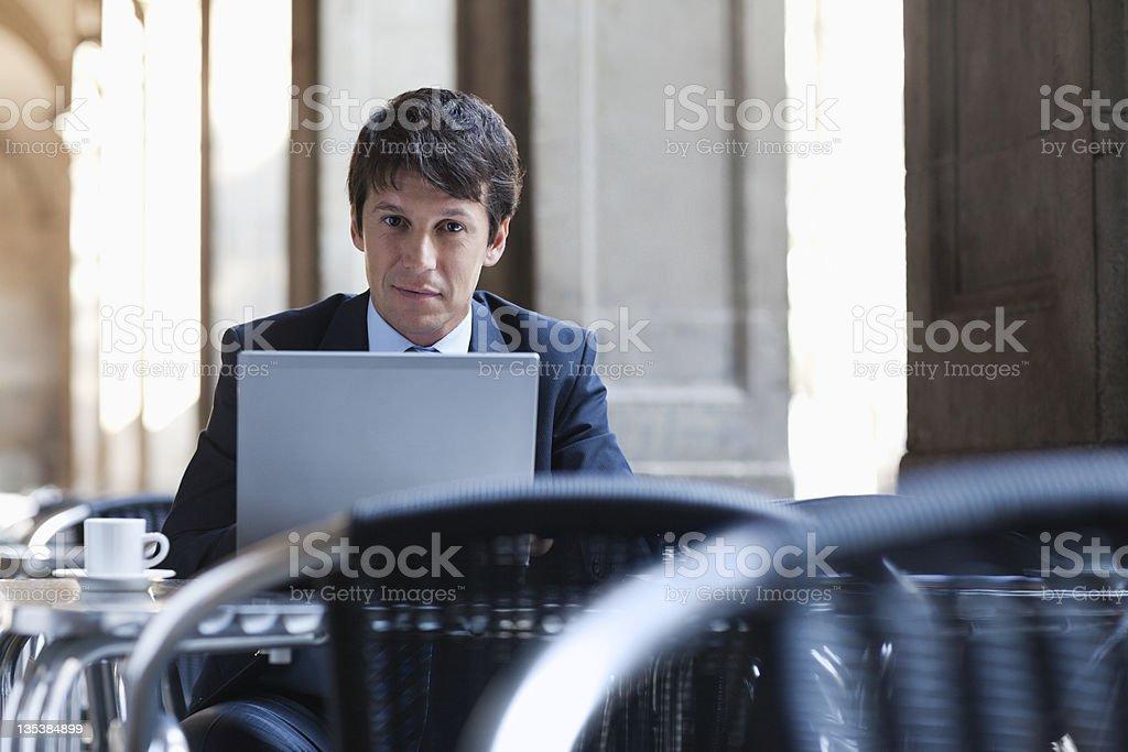 Businessman using laptop in sidewalk cafe royalty-free stock photo