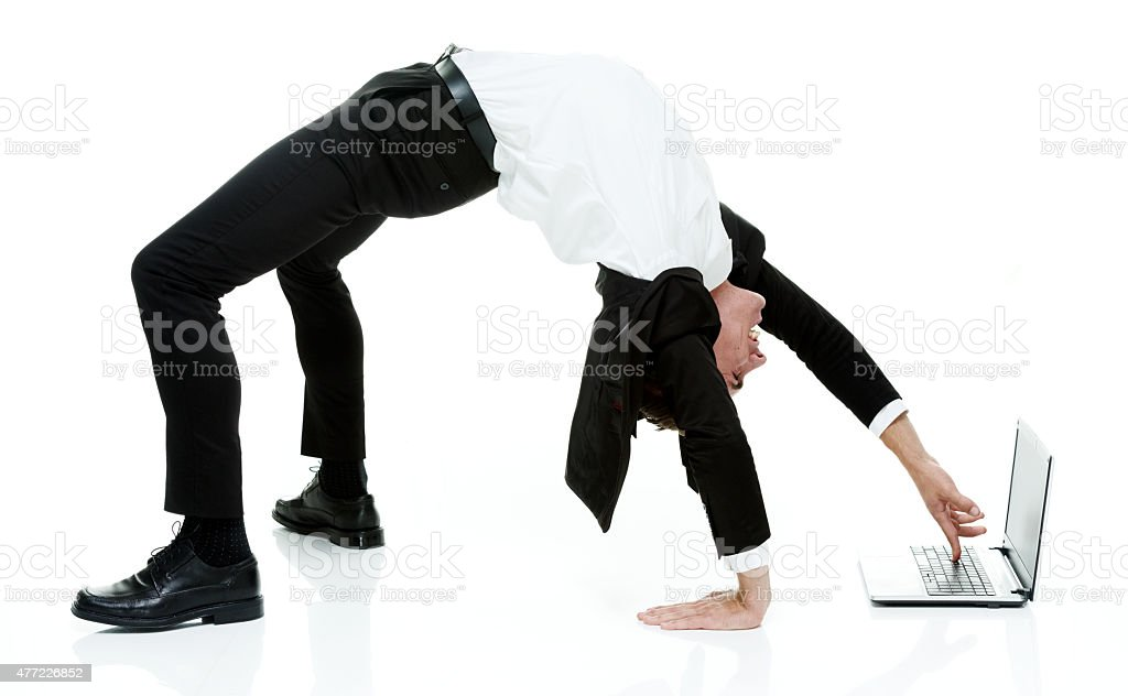 Businessman using laptop in yoga posture stock photo