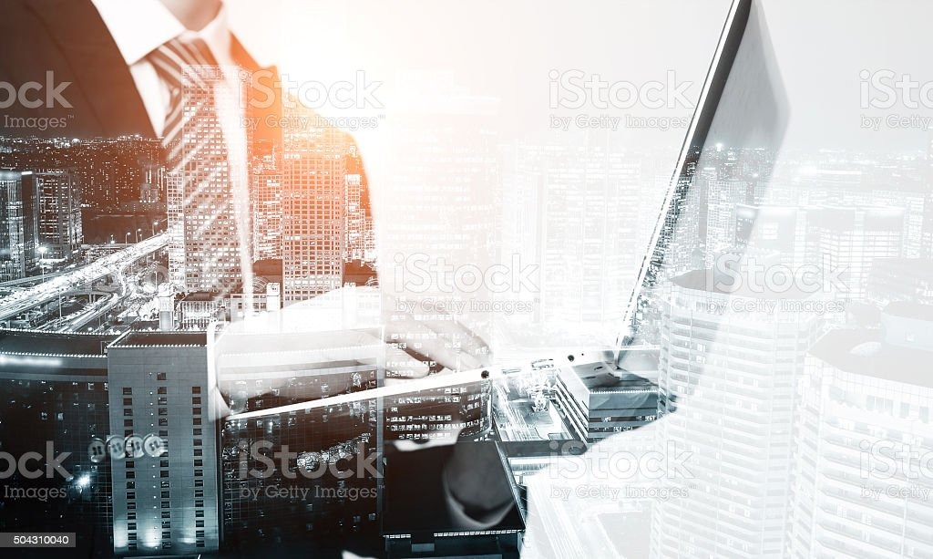 Businessman using laptop multiple exposure stock photo