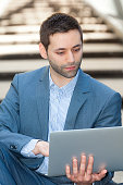 businessman using laptop sitting on stairs