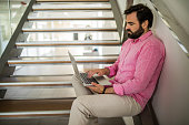 Businessman using laptop while relaxing on staircase.