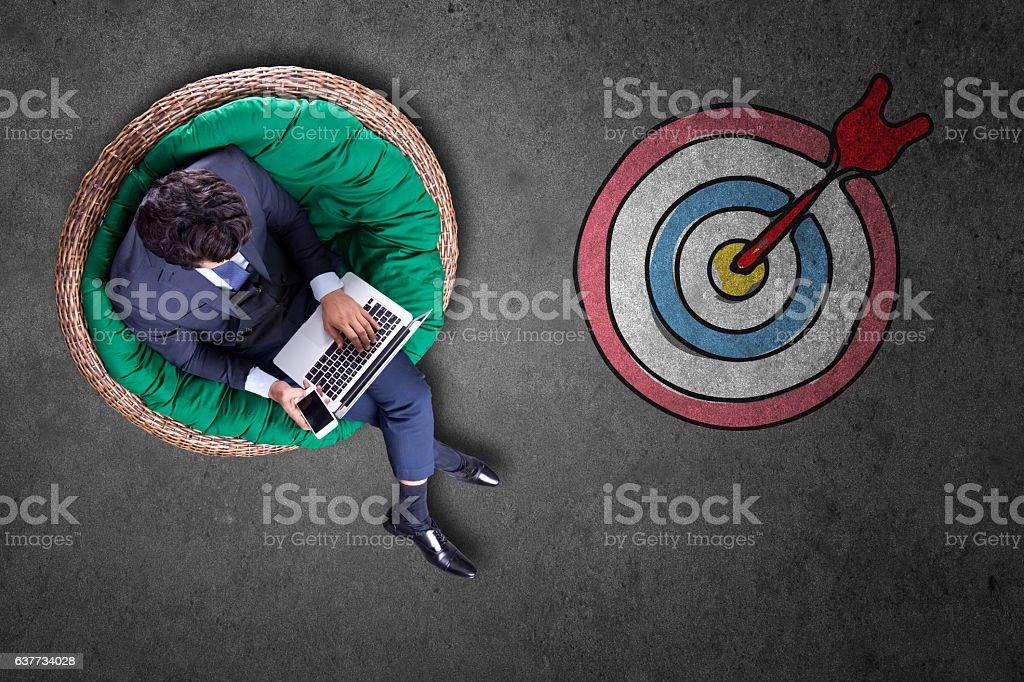 Businessman using laptop with bull's eye stock photo