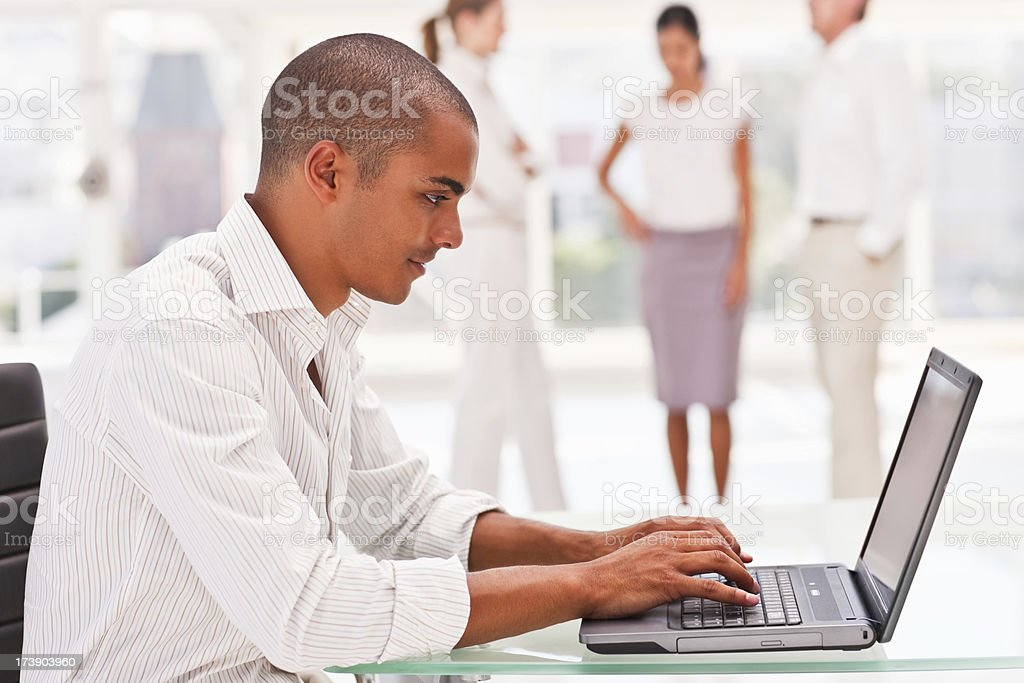 Businessman using laptop with colleagues in the background royalty-free stock photo