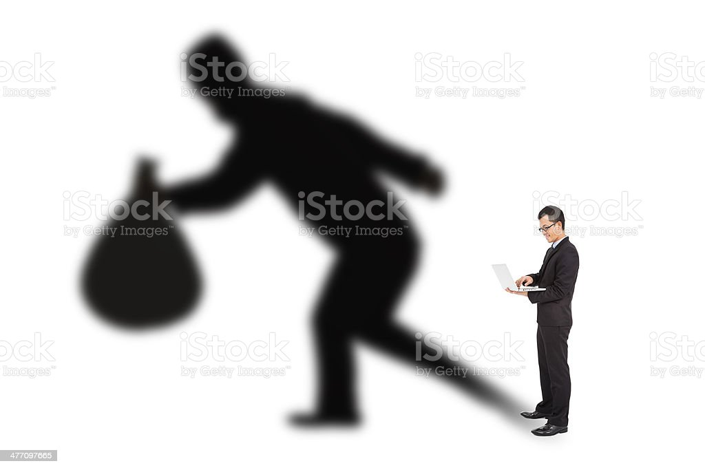 businessman using laptop with thief shadow stock photo