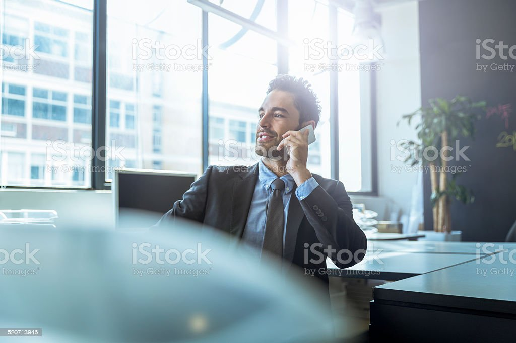 Businessman using mobile phone at desk stock photo