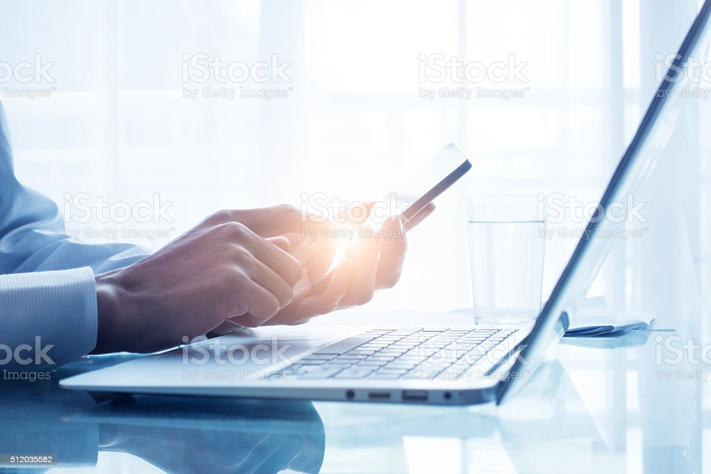 Businessman using mobile phone in office stock photo