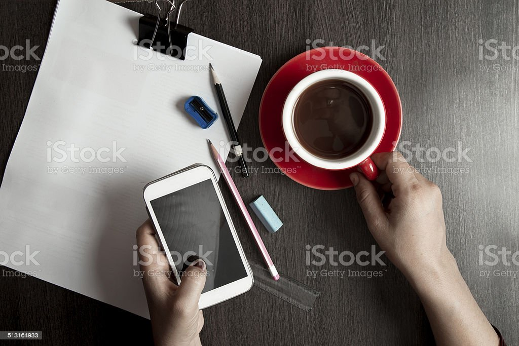 Businessman using mobile phone to analyse corporate reports stock photo