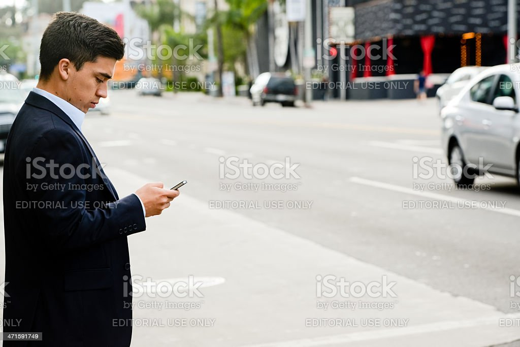 Businessman using mobile phone while crossing the street royalty-free stock photo