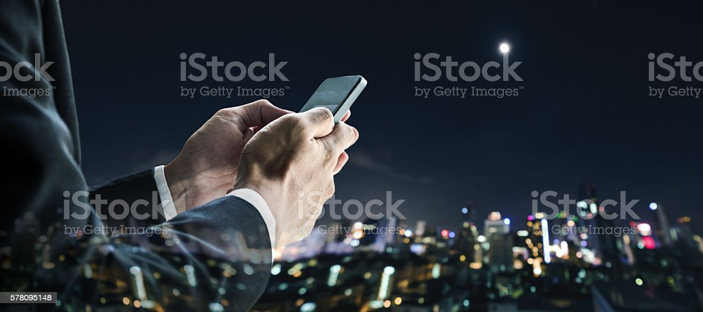 Businessman using mobile phone with defocus nightlife city background stock photo