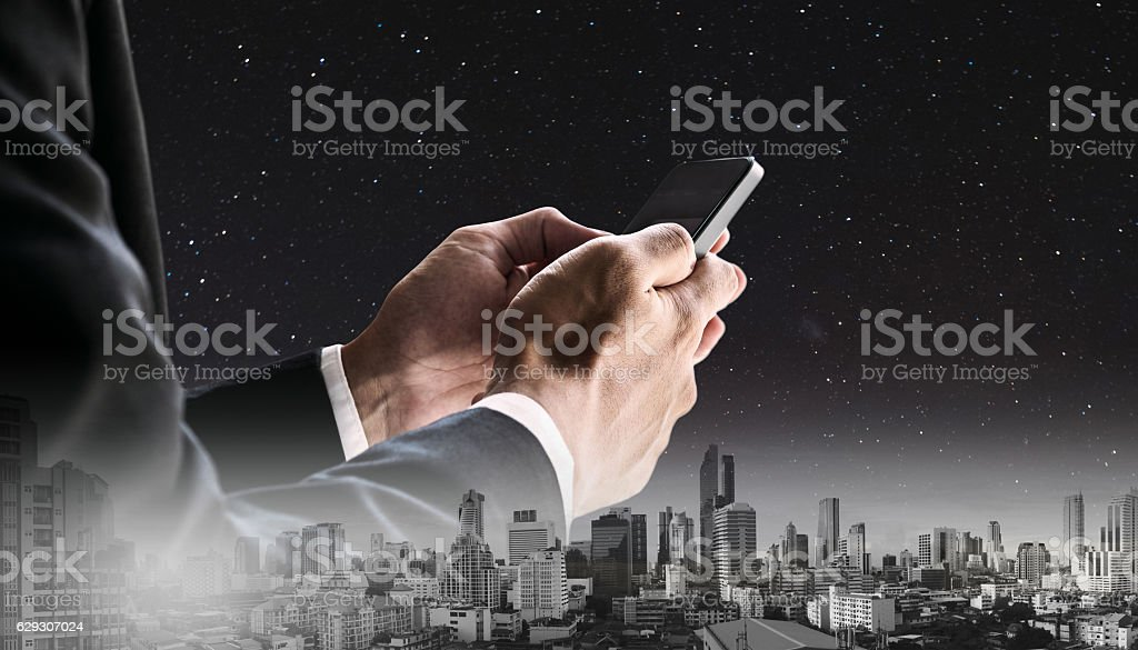 Businessman using mobile phone with panoramic cityscape at night stock photo