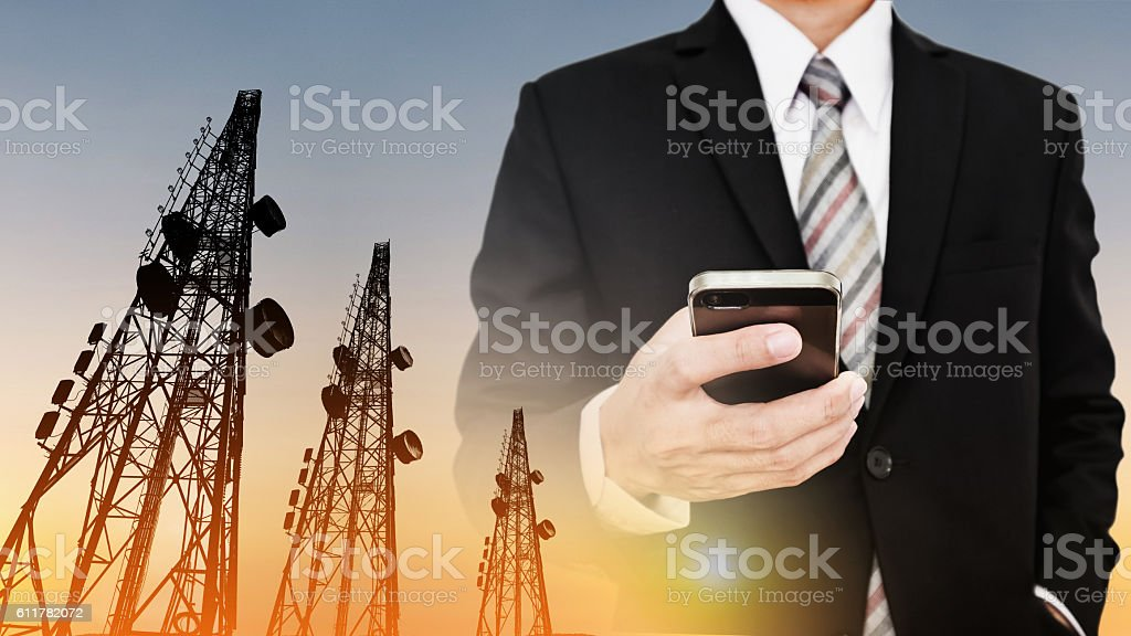 Businessman using mobile phone with Telecommunication towers stock photo