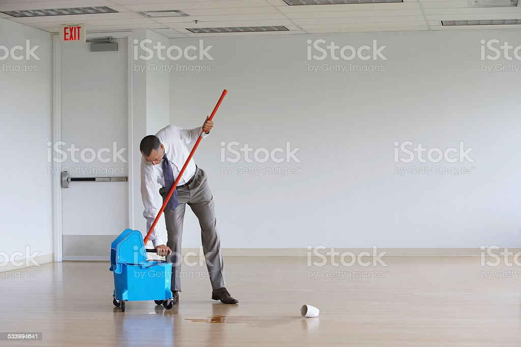 Businessman Using Mop In Empty Room stock photo