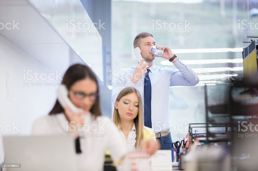 Businessman using phone while drinking water stock photo