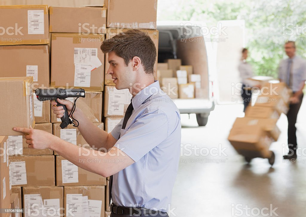 Businessman using scanner on box in warehouse stock photo
