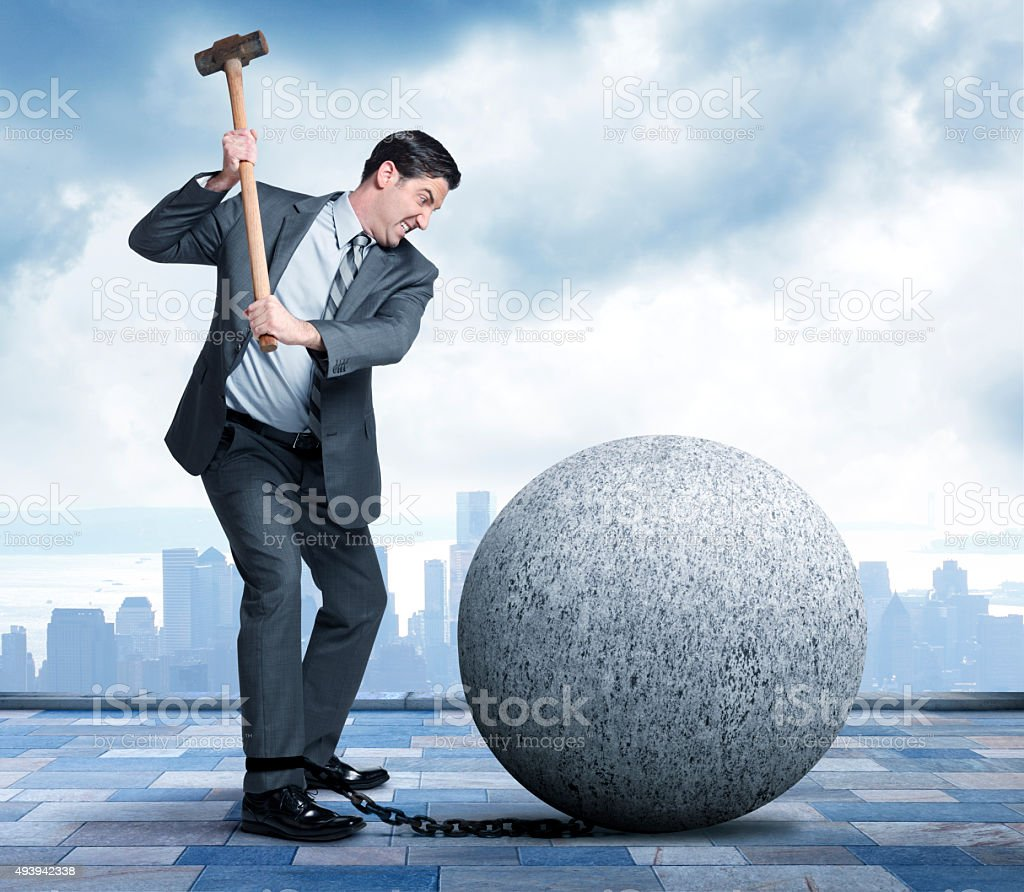 Businessman Using Sledgehammer To Break Free Of Ball And Chain stock photo