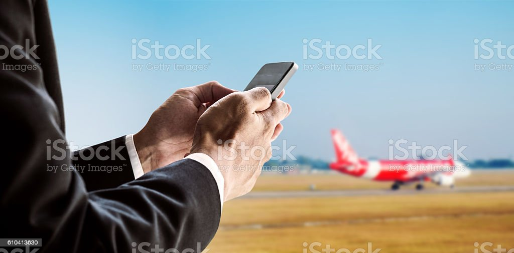 Businessman using smart phone with airplane background stock photo