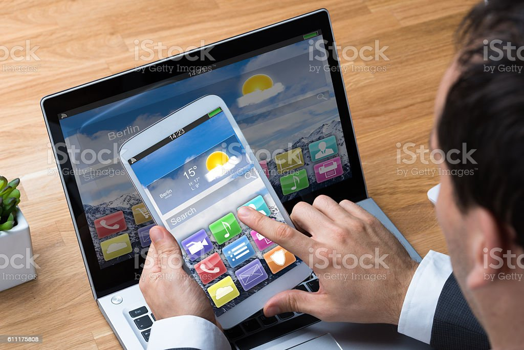 Businessman Using Smartphone And Laptop At Desk stock photo