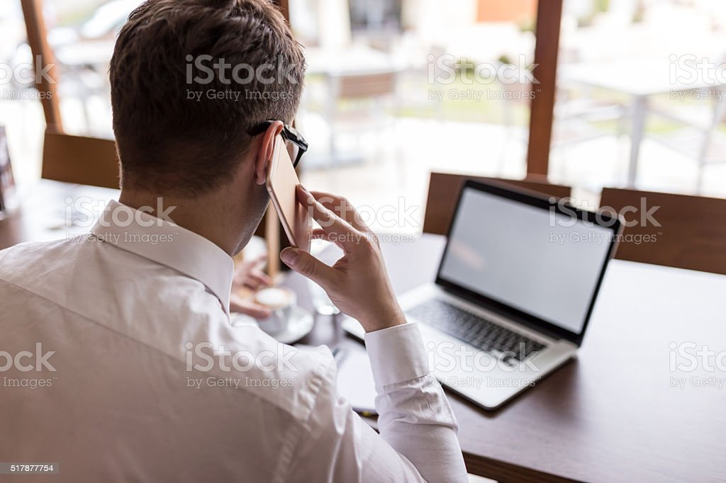 businessman using smartphone and laptop stock photo
