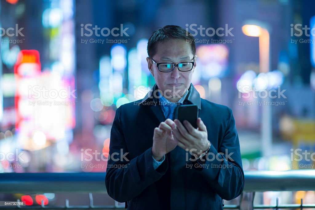 Businessman using smartphone at night. stock photo